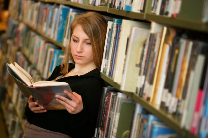 Girl in a library reading book