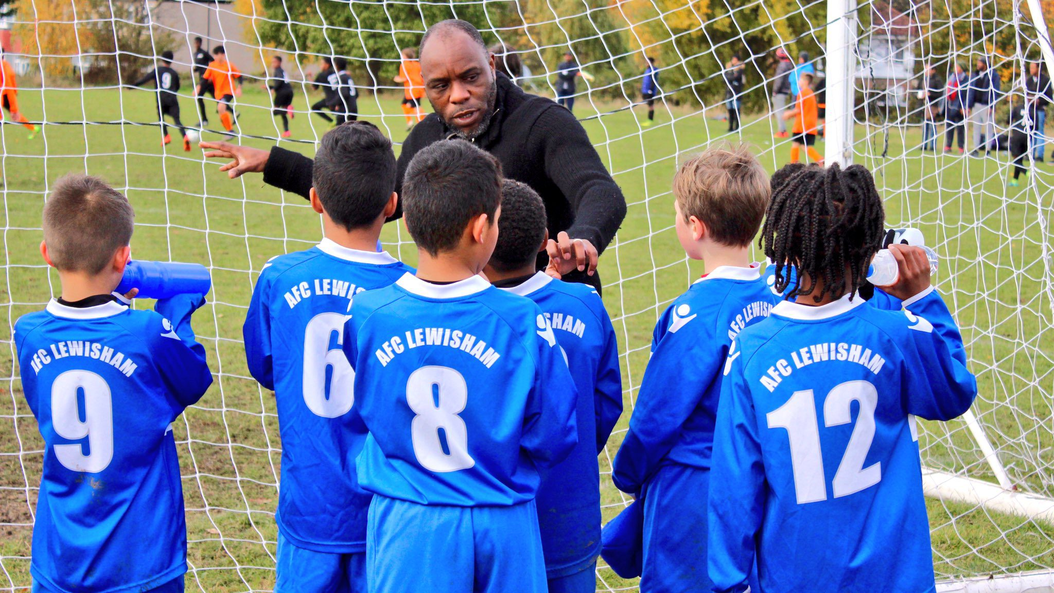 a football coach talks to a group of young players on the pitch