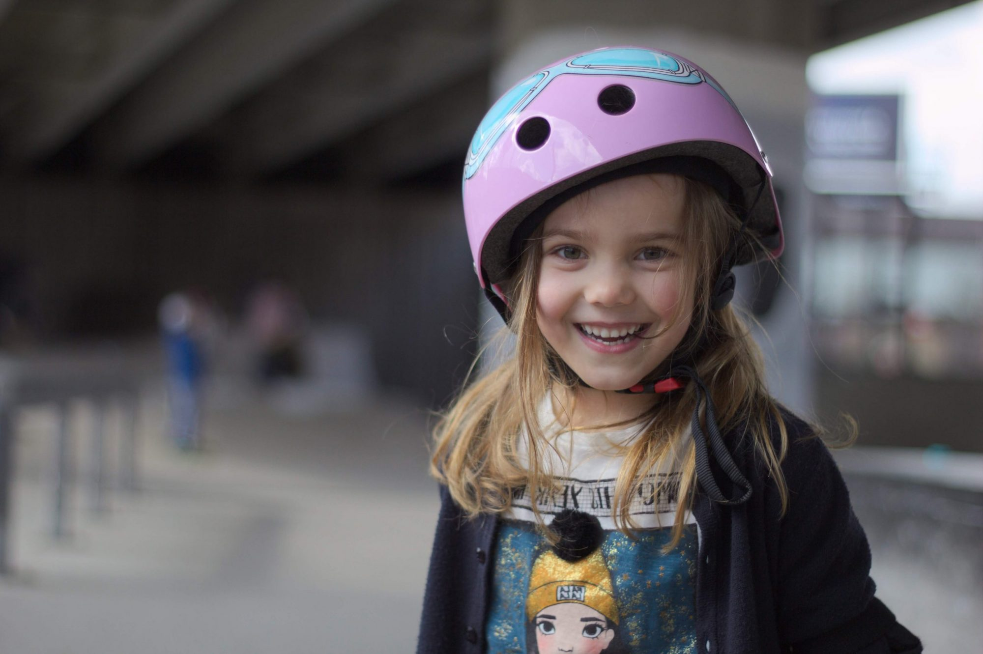 a young girl wearing a skate helmet grinning at the camera